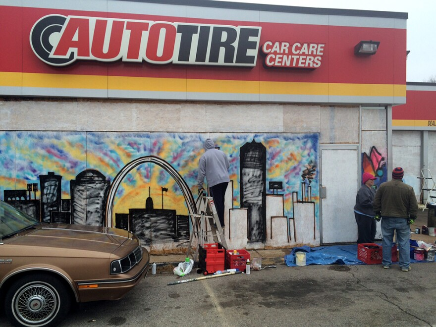Aaron Dickerson paints St. Louis cityscape on the plywood covering the windows of an auto parts shop in Dellwood on Saturday, December 6, 2014.