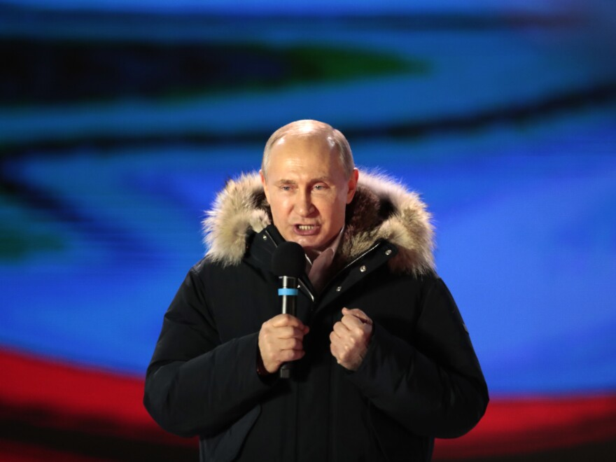 Russian President Vladimir Putin speaks during a rally near the Kremlin in Moscow, Sunday, after exit polls showed him handily winning a fourth term.
