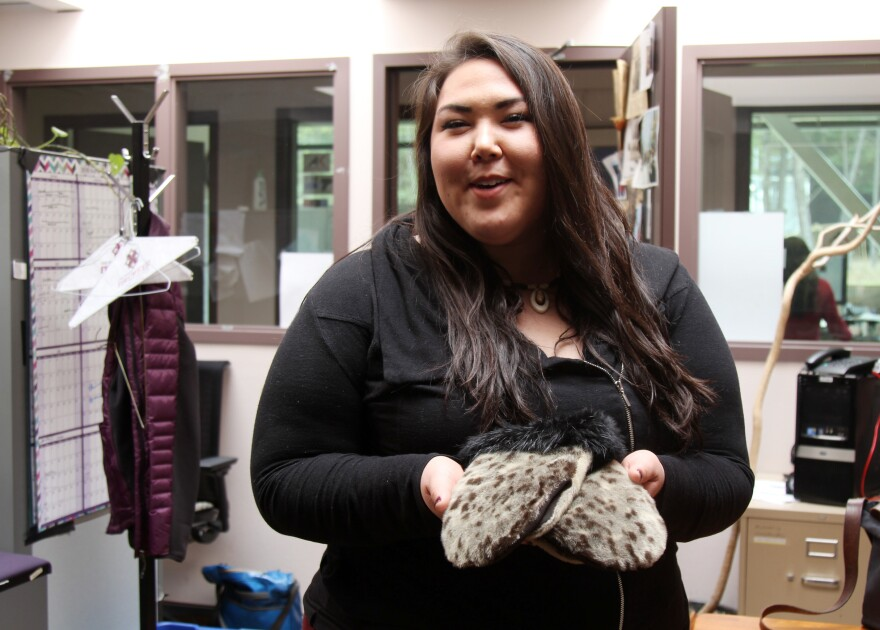 Cordelia Kellie showing off her sealskin gloves, made by a woman from Shishmaref and purchased at a dance festival.