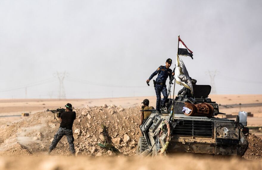 Iraqi pro-government forces hold a position on the frontline on Friday near the village of Tall al-Tibah, some 20 miles south of Mosul, during an operation to retake the hub city from the Islamic State group jihadists.