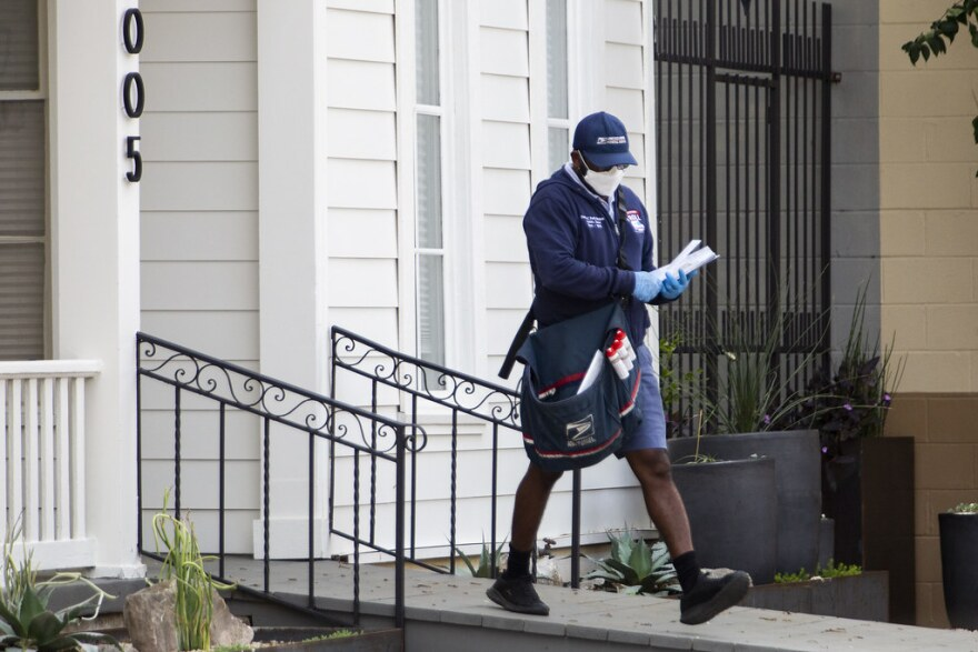 A United State Postal Service employee delivers mail while wearing a mask and gloves on March 27.