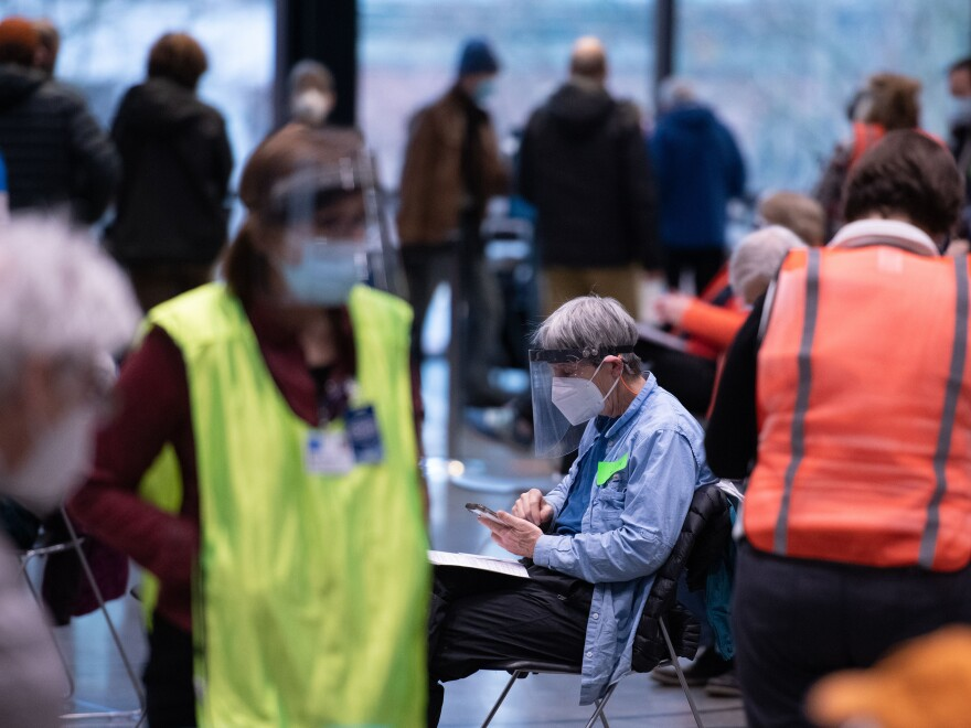 "Workers and patients at a pop-up COVID-19 vaccination site near downtown Seattle in January. ""The vast majority who are coming in do appear to be meeting the eligibility criteria,"" says Dr. Jeff Duchin, King County's public health officer."
