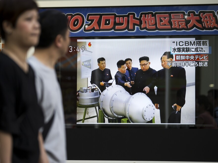 Pedestrians in Tokyo walk past a monitor showing an image of North Korean leader Kim Jong Un in a news program reporting on North Korea's sixth nuclear test on Sunday.