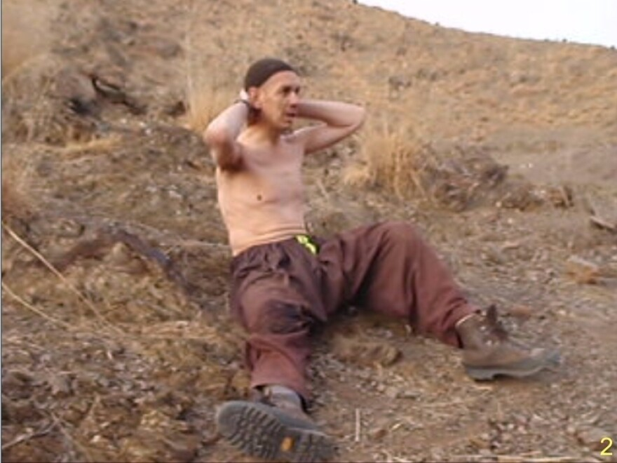 This photo provided by the U.S. Government, presented during a trial, shows a photo of Irek Hamidullin surrendering after being wounded by U.S. forces in Afghanistan on Nov. 29, 2009.