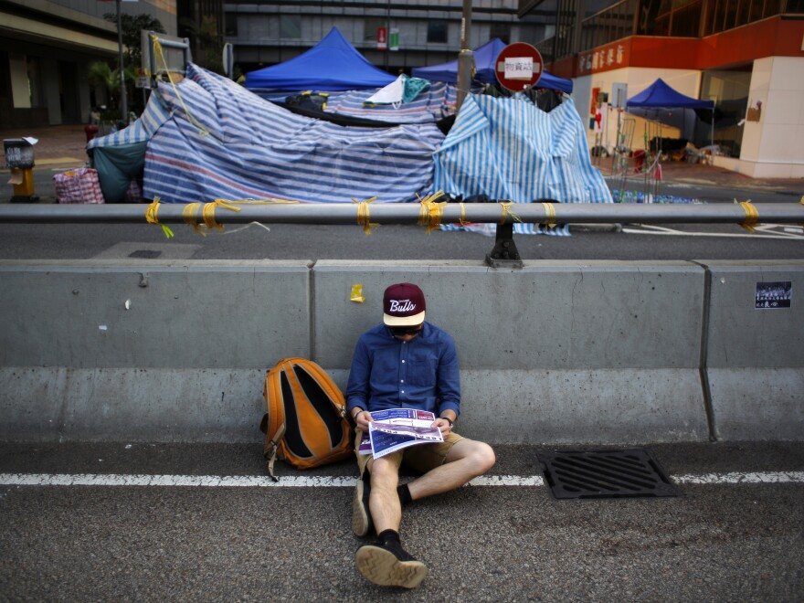 A protester sits along the main street to the financial Central district outside the government headquarters in Hong Kong.