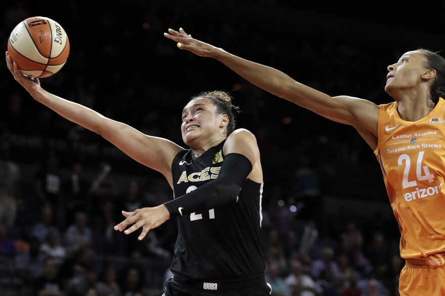 Las Vegas Aces guard Kayla McBride shoots around Phoenix Mercury forward DeWanna Bonner during the second half of a WNBA basketball game Wednesday, Aug. 1, 2018, in Las Vegas. The Aces refused to play a game in August 2018 citing injury risks, something no women's team had ever done. (John Locher/AP)