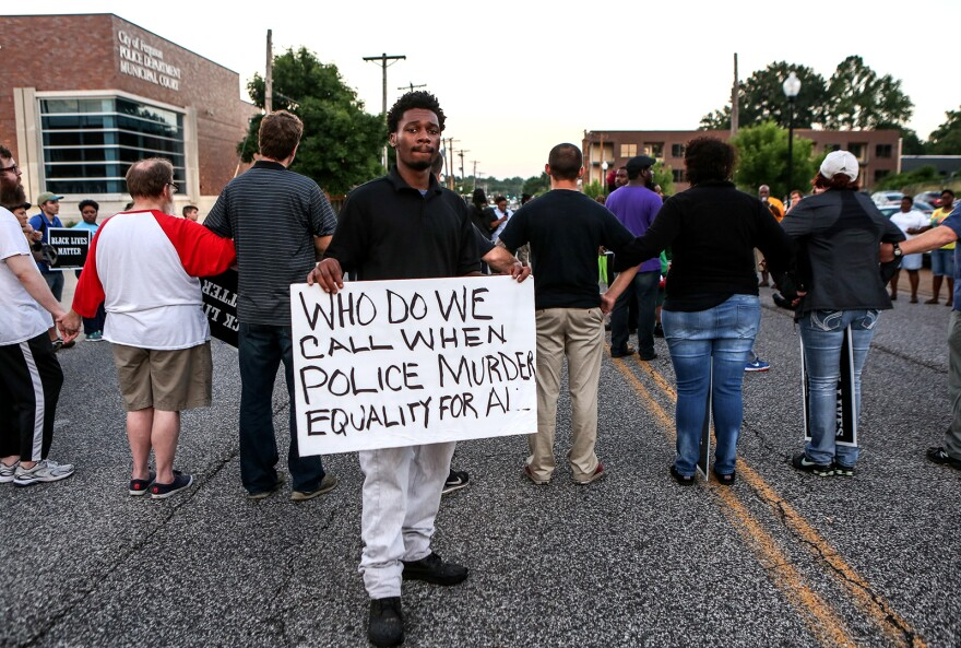 A crowd gathered at Ferguson police headquarters Wednesday night to stand in solidarity with Alton Sterling's community in Baton Rouge and continue to demand racial equality and police reform.
