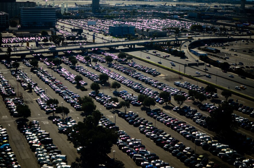 Mass of cars in a parking lot, lined up under the hot sun.