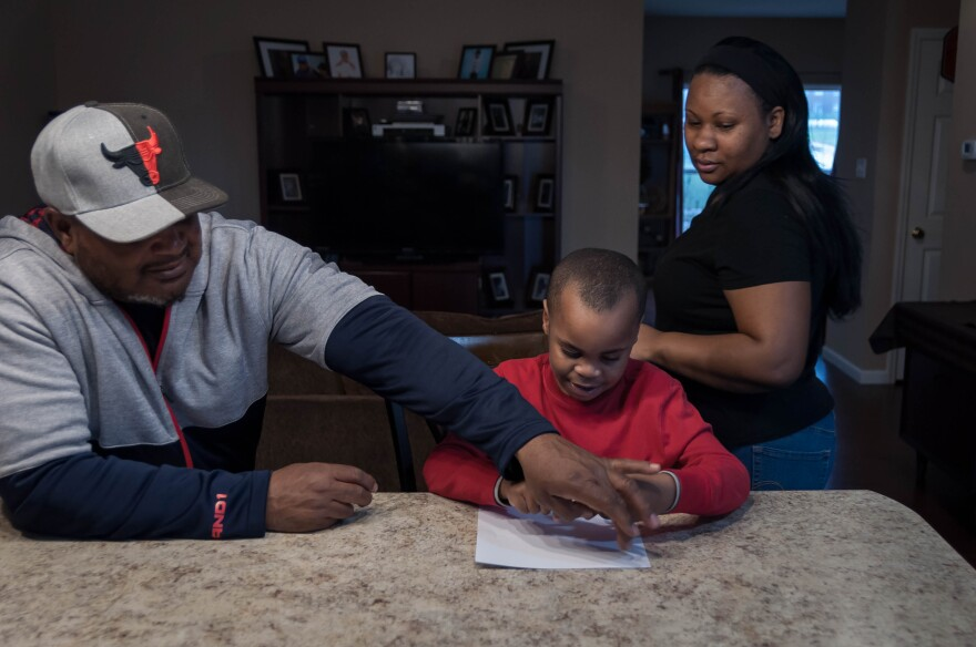 Michael and Elizabeth Carson watch their son, Isaiah, work on spelling colors in their home. The kindergartener at Gateway Elementary School missed a week of school with a respiratory infection.