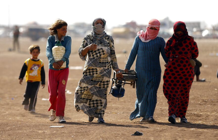 Syrian refugees who have left their homeland walk near the Turkish border town of Sanliurfa on Wednesday. The Islamic State assault against dozens of Kurdish villages in northern Syria has led to a mass exodus in recent days.