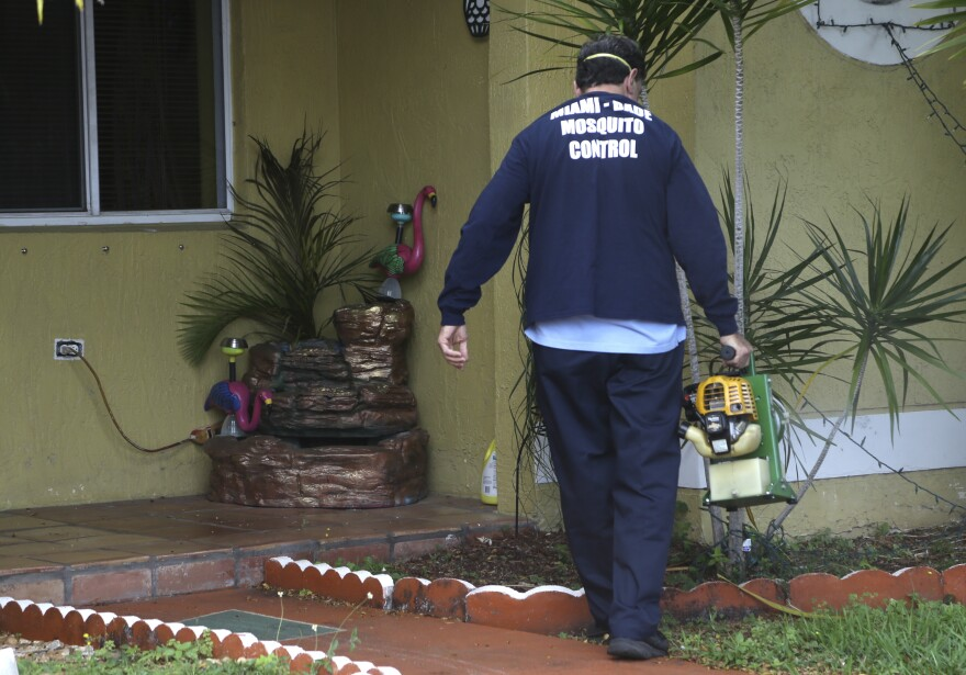 Giraldo Carratala, an inspector with the Miami Dade County mosquito control unit, sprays pesticide near a fountain where mosquito larvae were found in standing water in Miami.