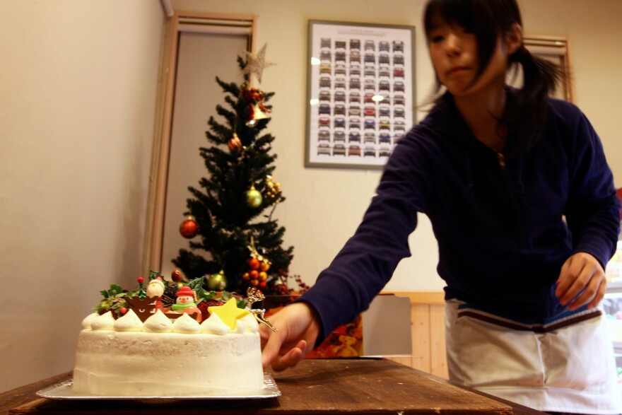 A woman prepares a Japanese Christmas cake at the Patisserie Akira Cake shop on Dec. 23, 2011. The sponge cake is drenched in symbolic meaning.