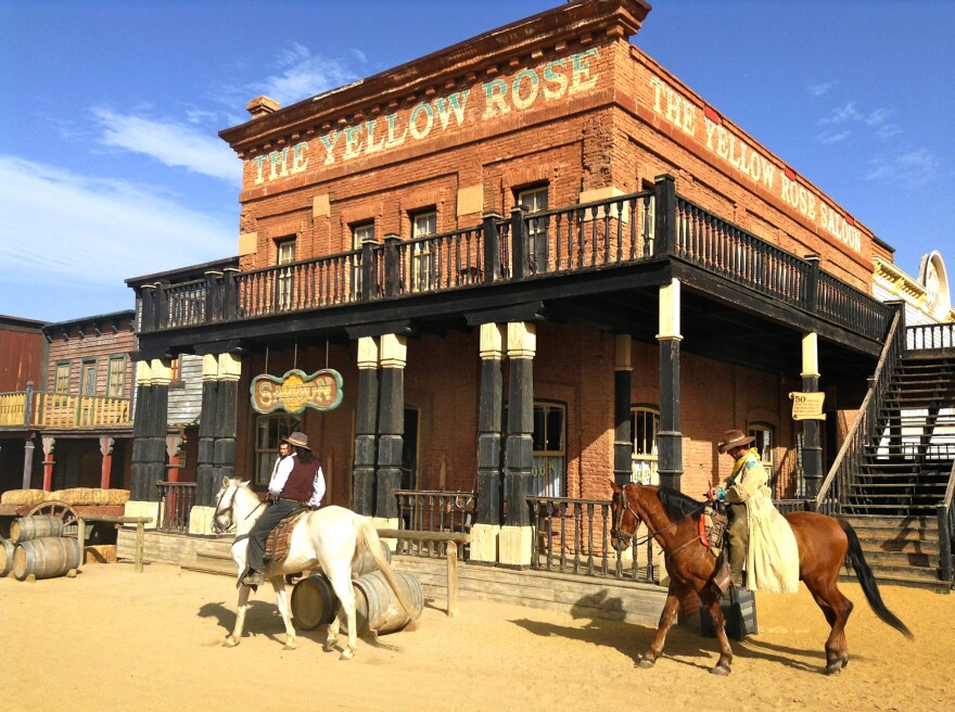 Actors roam in front of the Yellow Rose Saloon at the Oasys Theme Park, a tourist attraction built from abandoned film sets left over from the Spaghetti Westerns that were filmed in southern Spain's Tabernas Desert in the 1960s and 70s.