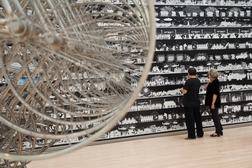 "Ai Weiwei and museum curator Sabine Eckmann examine ""The Odyssey,"" a massive frieze in his exhibition at the Mildred Lane Kemper Museum. In the foreground is a detail of ""Forever Bicycle,"" a sculpture made from 720 bicycles. [11/8/19]"