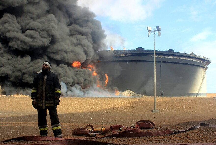 A Libyan fireman stands in front of a flaming oil storage tank in northern Libya's Ras Lanouf region on Jan. 23. It was set alight in fighting with the Islamic State, which has established a strong presence in the country and taken control of the city of Sirte.