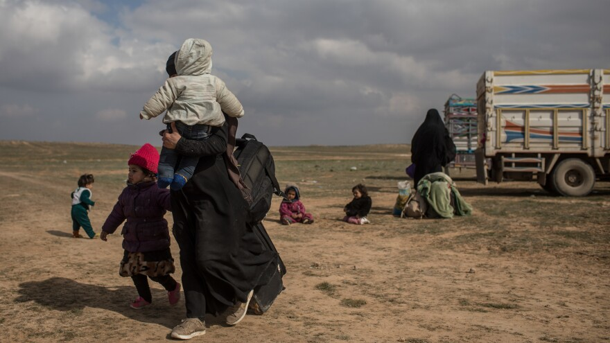 Civilians who have fled fighting in Bagouz wait to board trucks after being screened by members of the Syrian Democratic Forces (SDF) at a makeshift screening point in the desert on Saturday in Bagouz, Syria. After weeks of fighting the SDF announced the start of a final operation to oust ISIS from the last village held by the extremist group.