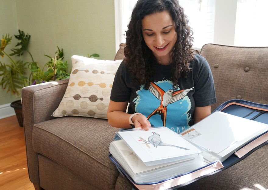 St. Louis illustrator Natalia Rojas flips through a binder of original illustrations she helped create for Wingspan on November 21, 2019.