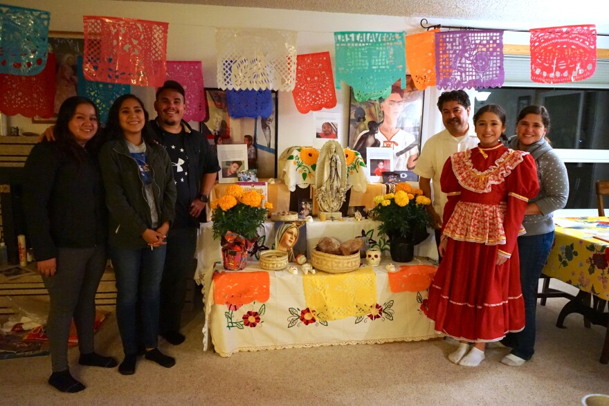 Family stands in front of altar decorated for day of the dead.