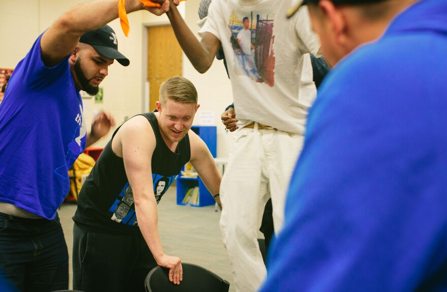 (From left) Marine veterans Richard Rivera and Dasovich help a youth participate in a trust-building exercise.