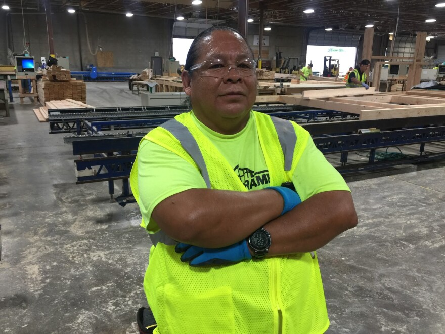 Yazzie stands with arms folded in a framing warehouse.