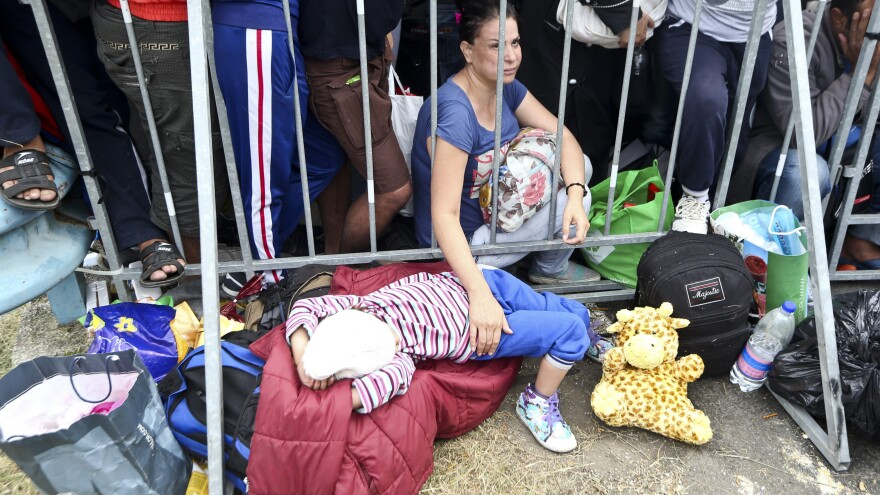 A migrant holds a child as they wait at the Croatia-Slovenia border crossing at Rigonce, Croatia, on Saturday.