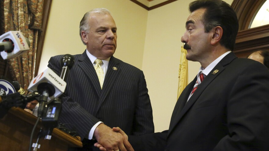 New Jersey Senate President Steve Sweeney (left) and Assembly Speaker Vincent Prieto shake hands as they announce an agreement to end the state budget impasse Monday night in Trenton.