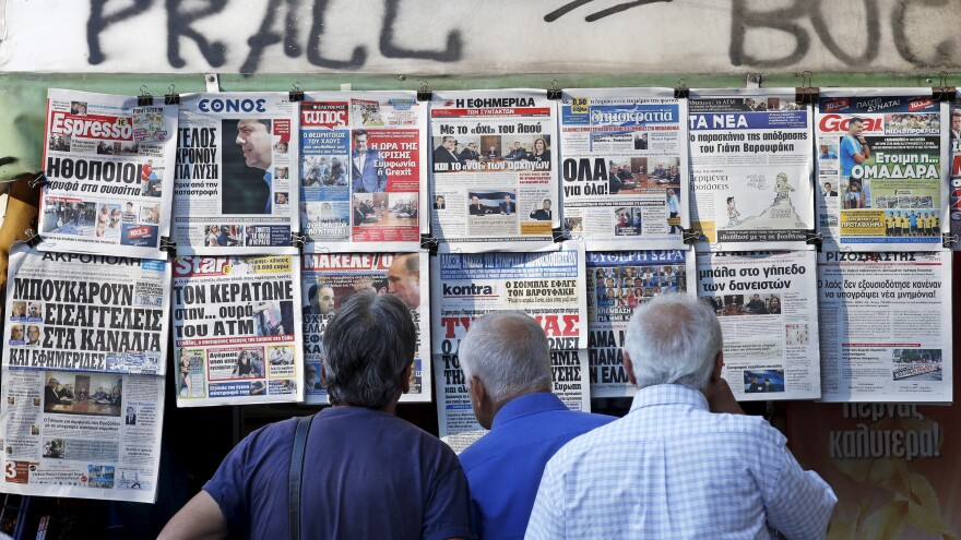 People read the front pages of various newspapers hanging at a kiosk Tuesday in central Athens. European leaders have set a Sunday deadline for Greece to reach a deal on debt repayment and austerity measures.