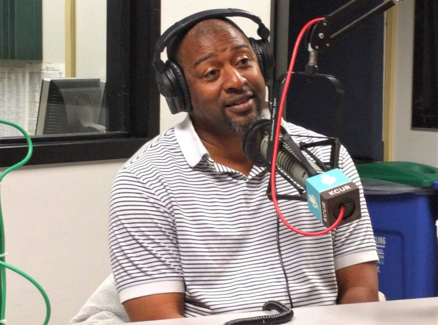 African American Chris Harris seated in front of a KCUR microphone wearing headphones during his interview.