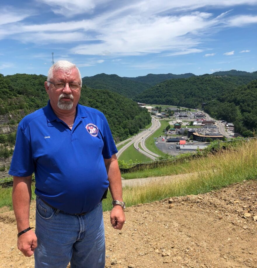 Doug Tackett, head of Pike County's emergency management division, stands at the top of the Pikeville Cut-Through in June. Officials cut a mountain in two in the 1970s, rerouting a river to avoid flooding. It was one of the largest land movements in the W