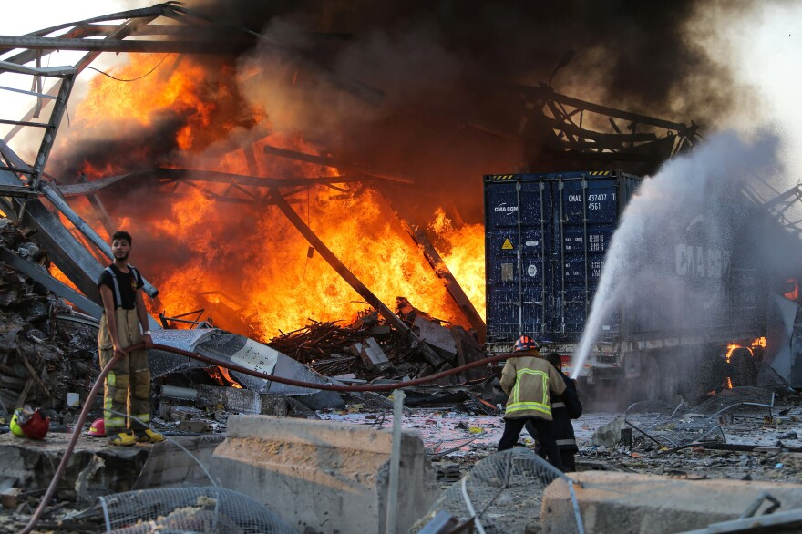 Firefighters douse a fire at Beirut's port. Hours after the blast, numerous Beirut hospitals are reportedly overwhelmed.