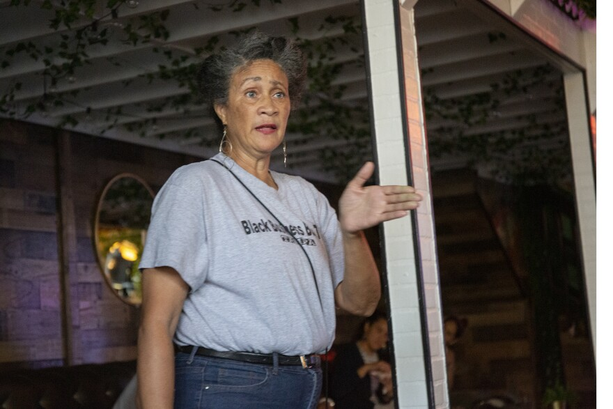 A woman wearing a gray shirt that says black business bus tour speaks to a group of people.