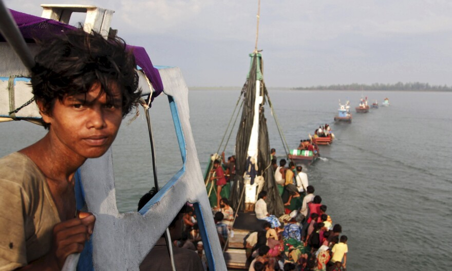 A fishing boat carrying Rohingya and Bangladeshi migrants is pulled to shore by Achenese fishermen off the coast of Julok, in Indonesia's Aceh province, on Wednesday.