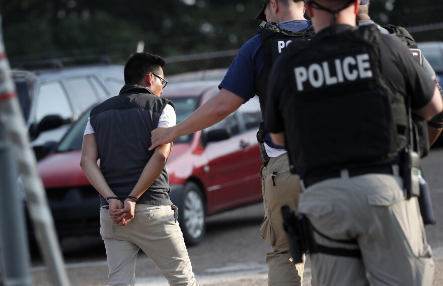 A man is taken into custody at a Koch Foods plant in Morton, Miss., on Aug. 7. U.S. immigration officials raided several Mississippi food processing plants and signaled that the early-morning strikes were part of a large-scale operation targeting owners as well as employees.