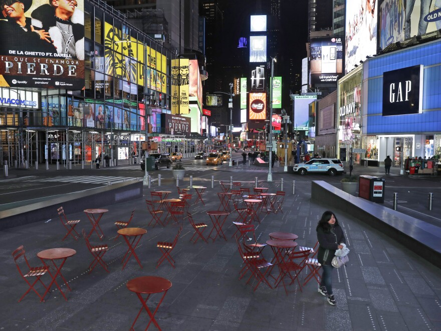 A woman walks through a nearly deserted Times Square in New York Monday, as the city adjusts to widespread closures and restrictions on public life because of the COVID-19 respiratory disease.