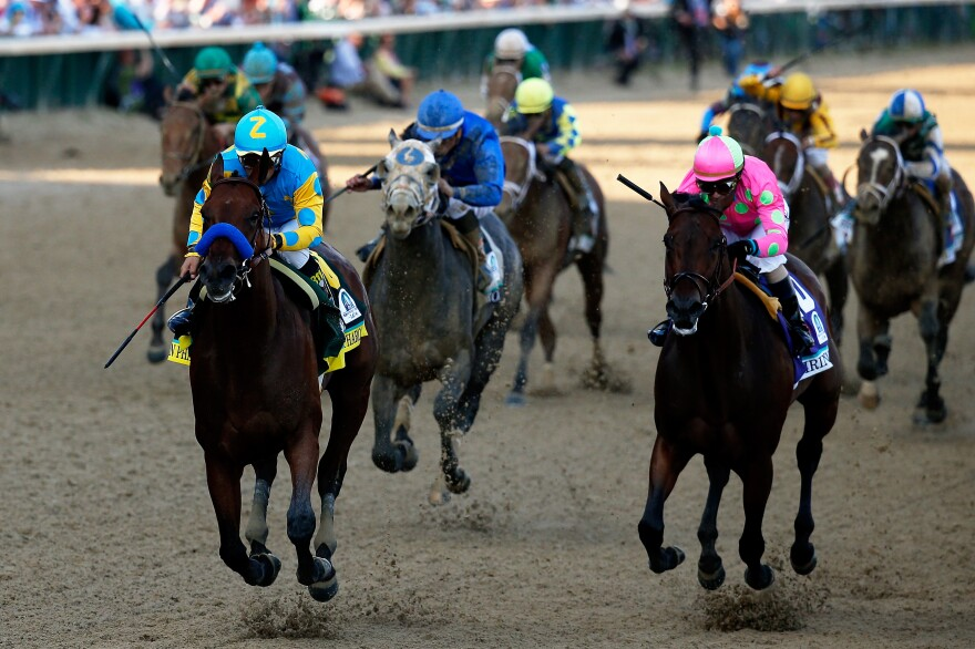 American Pharoah #18, ridden by Victor Espinoza (left), races Firing Line #10, ridden by Gary Stevens, out of turn 4 during the 141st running of the Kentucky Derby at Churchill Downs on Saturday.