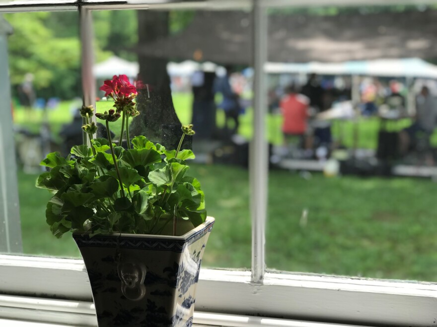 A potted flower sits in a window of the Happy Retreat mansion. Outside is the back lawn of the house. A temporary stage has been built for the Wine and Jazz Festival on June 9, 2018.