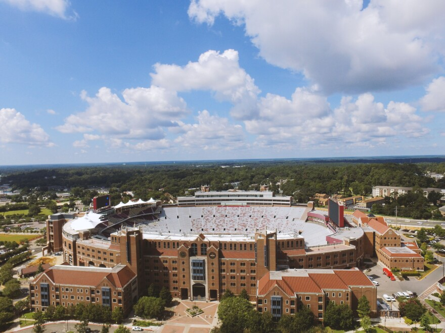 An aerial photo of a red brick football stadium. Green trees are in the back ground below a blue sky with white fluffy clouds.