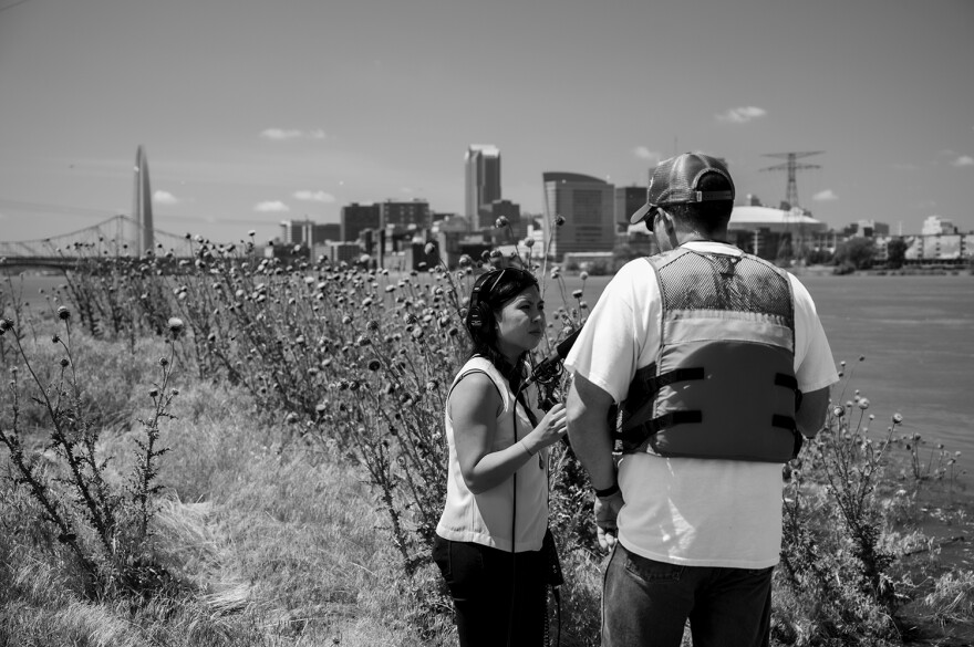 Reporter standing with microphone, conducting interview outside by the river.