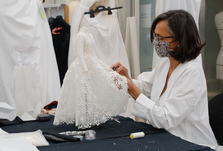 """An employee sews a miniature dress in Dior's sewing workshop in Paris on July 4. This year Dior created a miniature collection for its haute couture show and presented it <a href=""""https://www.youtube.com/watch?v=yxBFwqRbI8c"""">as a film</a>."""