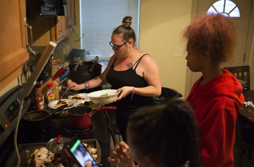 Regina Hartfield serves dinner for her children in their south St. Louis home. Hartfield said she's spent hours on the phone trying to get her children back on Medicaid.