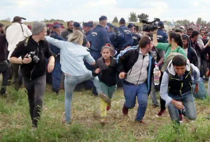Hungarian TV camerawoman Petra Laszlo is seen sticking out her leg as a young girl and other migrants run from a police line at Roszke, in southern Hungary, in September 2015.