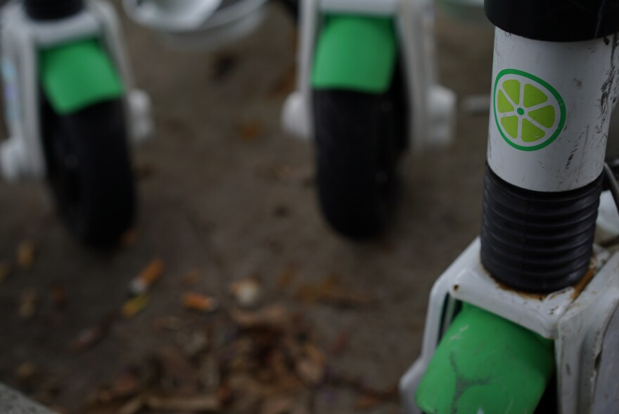 Lime's logo-a sliced lime-is displayed above the wheel of an e-scooter. The wheels of two other e-scooters are in the background.