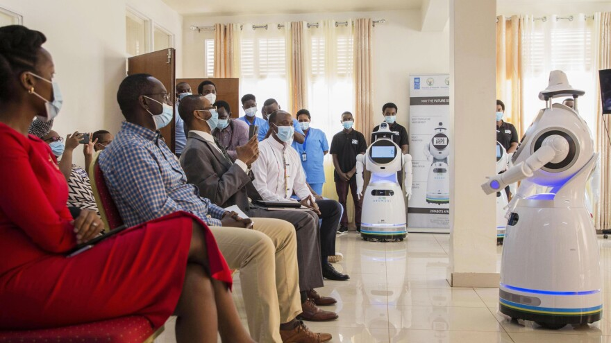 """A robot introduces itself to patients in Kigali, Rwanda. The robots, used in Rwanda's treatment centers, can screen people for COVID-19 and deliver food and medication, among other tasks. The robots were donated by the United Nations Development Program and the <a href=""""https://minict.gov.rw/home/"""">Rwanda Ministry of ICT and Innovation.</a>"""