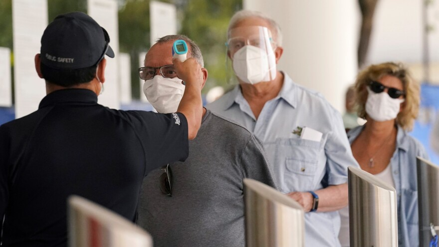In this Feb. 8, 2021, file photo, Florida seniors have their temperatures taken before receiving the second dose of the Pfizer COVID-19 vaccine at Jackson Health System in Miami.