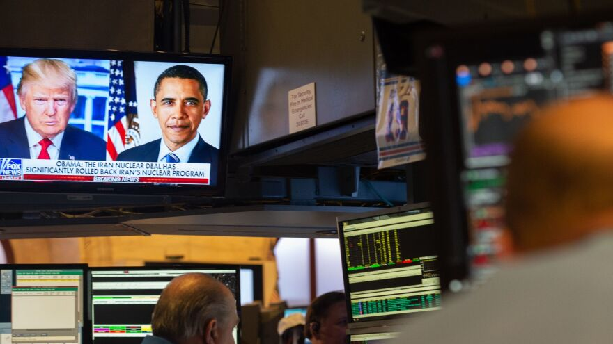Images of President Trump and former President Barack Obama are on television as traders work on the floor of the New York Stock Exchange.