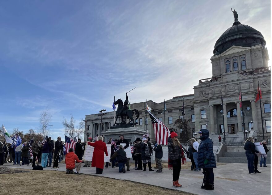 People holding American and Trump flags mill around the Montana Capitol complex wearing puffy jackets.