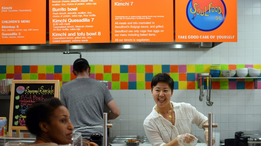 """Anna Goree (right) talks to customer Tioni Collins while Anna's husband, Jon Goree, prepares the food at Seoul Food D.C. restaurant, which is located inside an Exxon gas station. """"My wife Anna is not only an excellent cook; she knows everyone by name and has good rapport with our customers,"""" Jon tells The Salt."""