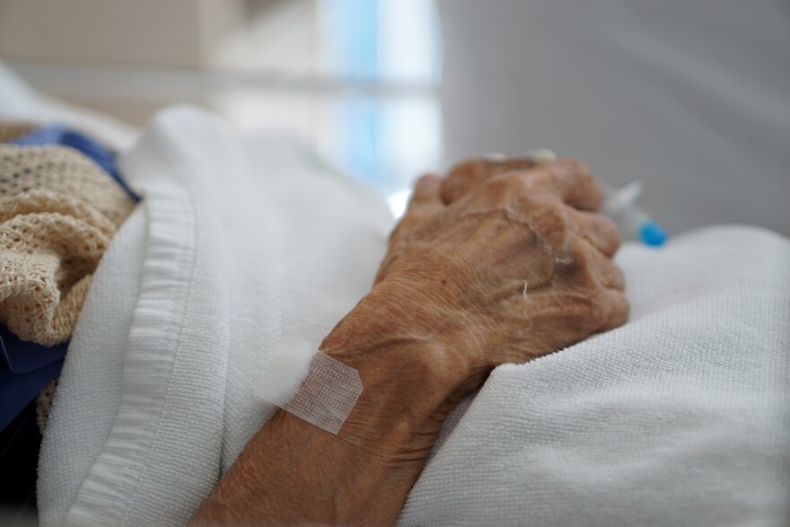 Closeup hand of sick elderly patient lying on the bed in hospital