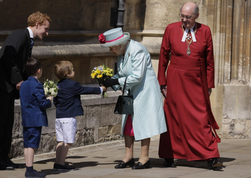 Britain's Queen Elizabeth II is presented with flowers after attending the Easter Matins Service at St. George's Chapel in Windsor, England.