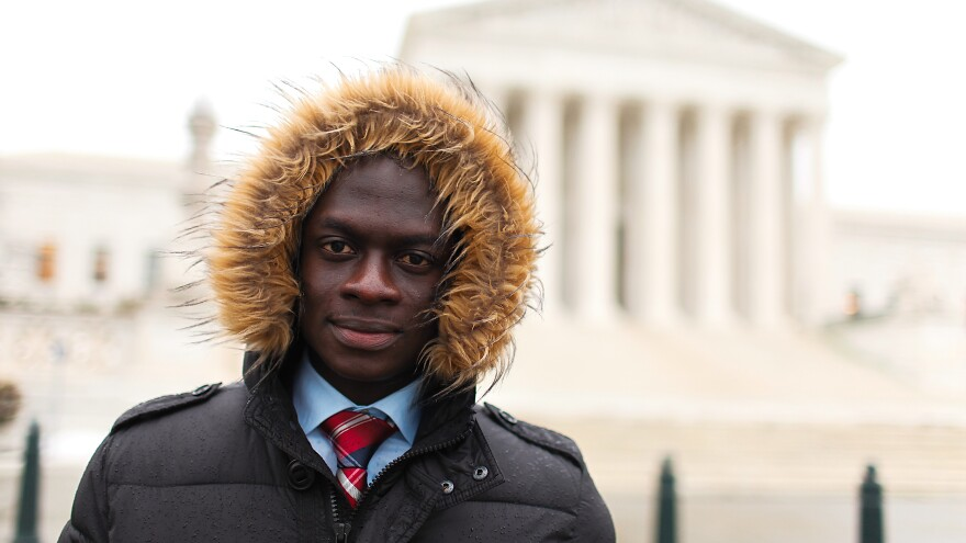 "Tarkpor Mambia in front of the Supreme Court in Washington, D.C. He says he ""literally froze"" during his first American winter in 2013, but is getting used to the cold weather."